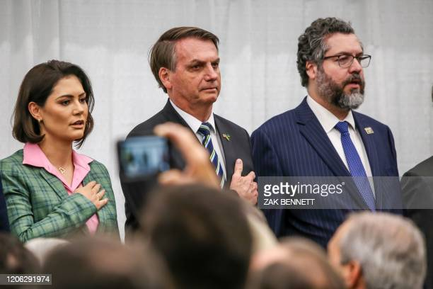 Brazilian President Jair Bolsonaro alongside Brazil's Minister of Foreign Affairs Ernesto Araujo look on during the Brazilian national anthem in...