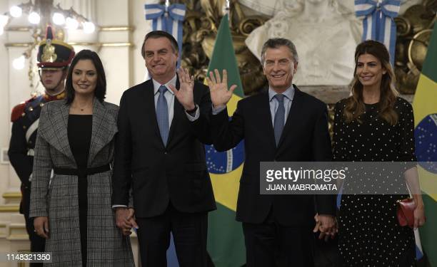 Brazilian President Jair Bolsonaro and his wife Michelle de Paula Firmo pose with Argentina's President Mauricio Macri and his wife Juliana Awada...