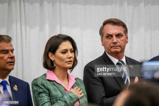 Brazilian President Jair Bolsonaro and wife Michelle Bolsonaro stand during the Brazilian national anthem in front of Miami's Brazilian community at...