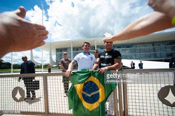 Brazilian President Jair Bolsonaro appears and greets supporters amidst the outbreak of the coronavirus at the Palacio do Planalto March 2020 in...