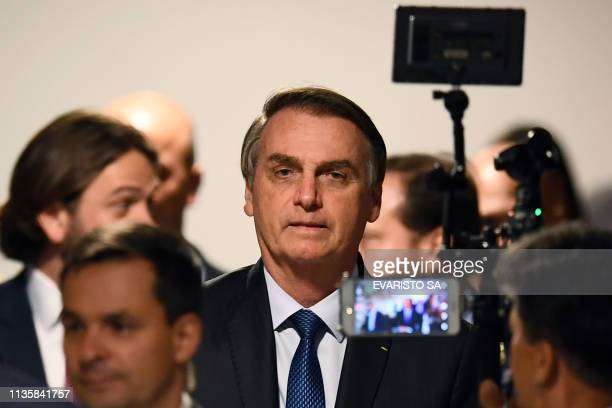 Brazilian President Jair Bolsonaro arrives at ceremony to sanction a law that will offer lower bank rates for people who do not have debts at...
