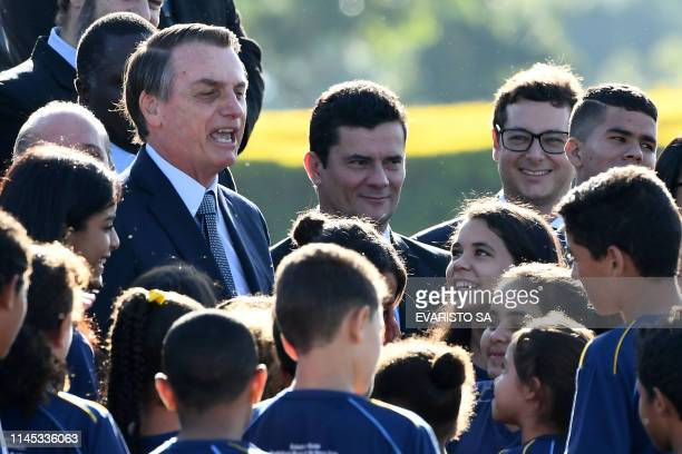 Brazilian President Jair Bolsonaro attends the Brazilian flag hoisting ceremony next to his Justice Minister Sergio Moro at the Alvorada Palace in...