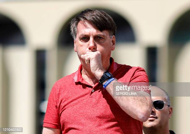 Brazilian President Jair Bolsonaro coughs as he speaks after joining his supporters who were taking part in a motorcade to protest against quarantine...