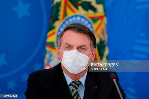 TOPSHOT Brazilian President Jair Bolsonaro covers his face with a face mask during a press conference regarding the COVID19 coronavirus pandemic at...