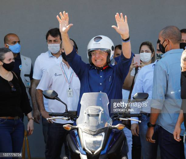Brazilian President Jair Bolsonaro gestures after going out for a ride and having his motorcycle's engine overhaul after he announced he tested...
