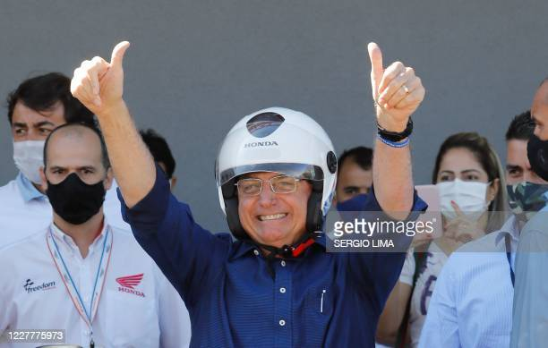 TOPSHOT Brazilian President Jair Bolsonaro gestures after going out for a ride and having his motorcycle's engine overhaul after he announced he...