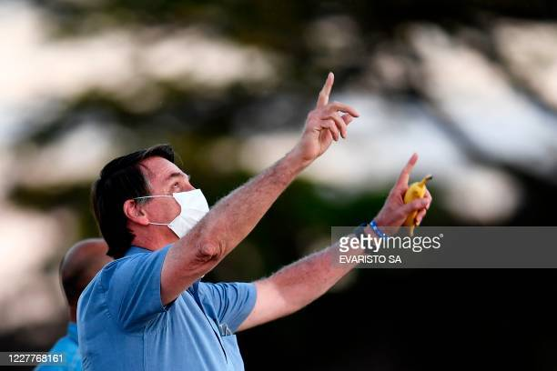TOPSHOT Brazilian President Jair Bolsonaro gestures as he speaks to supporters while holding a banana in his hand in the garden of the Alvorada...
