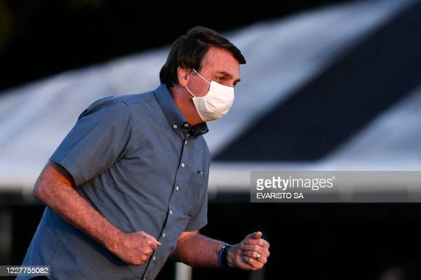 Brazilian President Jair Bolsonaro gestures at supporters after the flag unveiling ceremony at the Alvorada Palace in Brasilia on July 23 2020