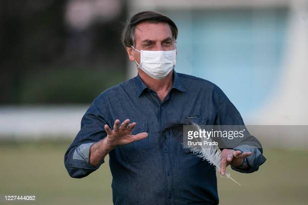 Brazilian President Jair Bolsonaro gestures in front of the official residence after testing positive for coronavirus in Alvorada Palace on July 15,...
