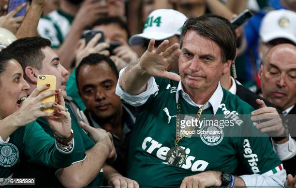 Brazilian President Jair Bolsonaro gestures with Palmeiras fans during a match between Palmeiras and Vasco for the Brasileirao Series A 2019 at...