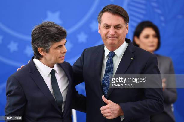 Brazilian President Jair Bolsonaro gives the thumb up as he embraces his new Health Minister Nelson Teich during his swearingin ceremony at Planalto...