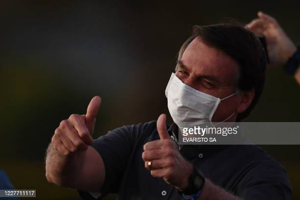 Brazilian President Jair Bolsonaro gives the thumbs up to supporters from the Alvorada Palace in Brasilia on July 20 amid the new coronavirus pandemic