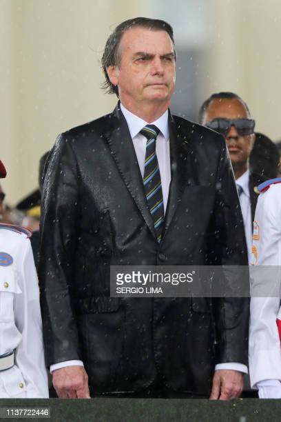 Brazilian President Jair Bolsonaro is drenched with rain as he attends a ceremony to mark Army Day in Brasilia on April 17 two days ahead of the...