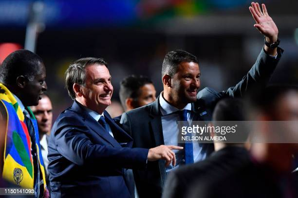 Brazilian President Jair Bolsonaro is pictured next to Brazilian former footballer Washington and congressman Helio during the Copa America football...