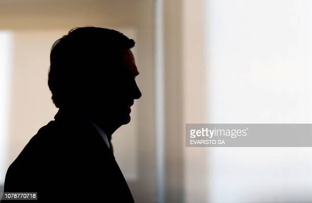 TOPSHOT Brazilian President Jair Bolsonaro is silhouetted during the appointment ceremony of the new heads of public banks at Planalto Palace in...