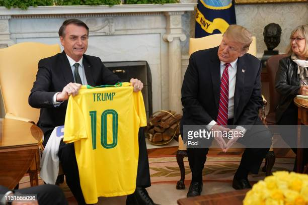 Brazilian President Jair Bolsonaro presents US President Donald Trump with a Brazil national soccer team jersey Number 10 for striker position at the...
