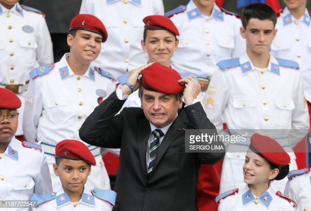 TOPSHOT Brazilian President Jair Bolsonaro puts a beret on as he poses with students of the Military College during a ceremony to mark Army Day in...
