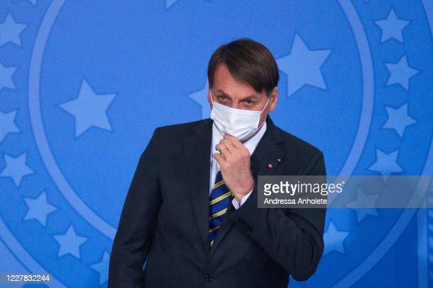 Brazilian President Jair Bolsonaro puts his hand on the protective mask during the launch of the Rural Women Campaign amidst the coronavirus pandemic...