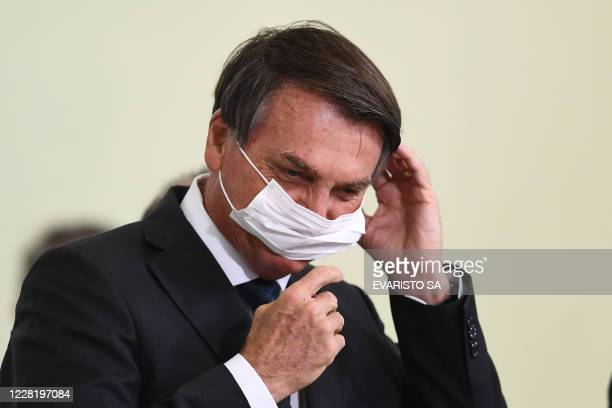"""Brazilian President Jair Bolsonaro puts on a facemask during the launch of the new housing program """"Casa Verde e Amarelo"""" at Planalto Palace in..."""