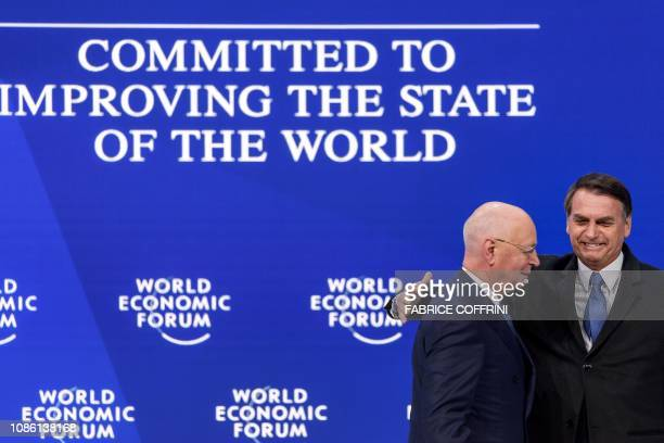 Brazilian President Jair Bolsonaro reacts with Founder and Executive Chairman of the World Economic Forum Klaus Schwab after delivering a speech...