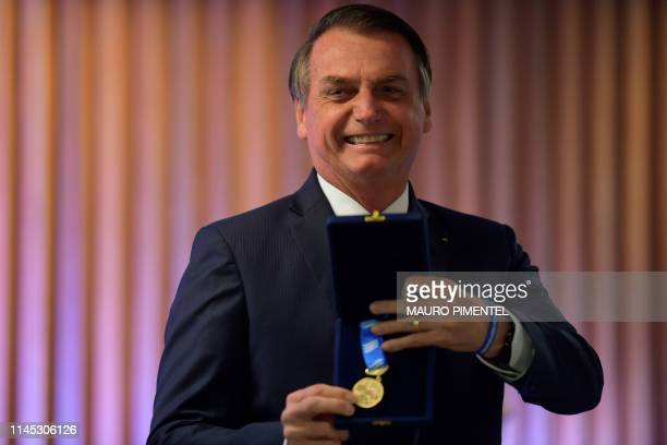 Brazilian President Jair Bolsonaro receives a medal at the Federation of Industries of Rio de Janeiro headquarters in Rio de Janeiro on May 20 2019