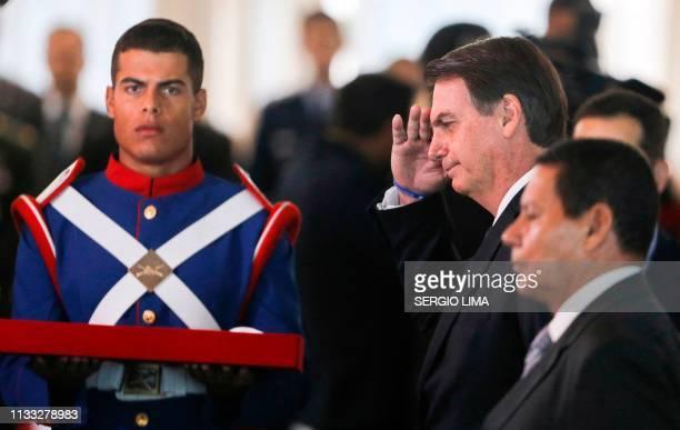 Brazilian President Jair Bolsonaro salutes as he and VicePresident Hamilton Mourao are awarded the Order of Military Judiciary Merit in Brasilia on...