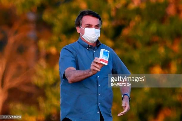 TOPSHOT Brazilian President Jair Bolsonaro shows a box of hydroxychloroquine to supporters outside the Alvorada Palace in Brasilia on July 23 2020 In...