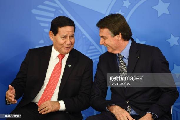Brazilian President Jair Bolsonaro speaks with his vicepresident Hamilton Mourao during a ceremony to pass the Economic Freedom Act at Planalto...