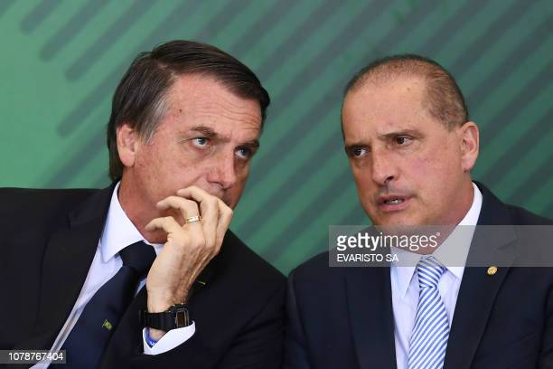 Brazilian President Jair Bolsonaro talks to Chief of Staff Onyx Lorenzoni during the appointment ceremony of the new heads of public banks at...