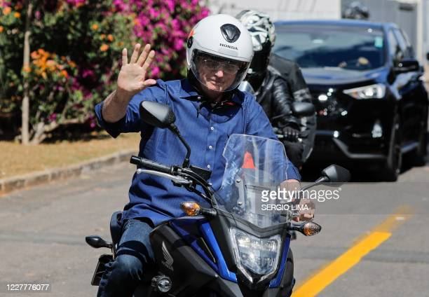 TOPSHOT Brazilian President Jair Bolsonaro waves as he takes a ride and has his motorcycle's engine overhaul after he announced he tested negative...