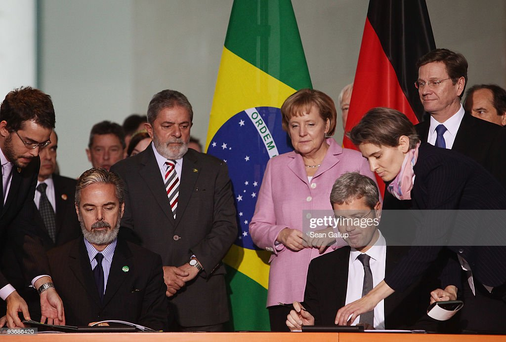 Brazilian President Luiz Inacio Lula da Silva (C-L), German Chancellor Angela Merkel (C) and German Foreign Minister Guido Westerwelle (R) watch as Brazilian Ambassador to German Everton Vieira Vargas (L) and German Environment Minister Norbert Roettgen sign an aggreement on mutual efforts to combat climate change on December 3, 2009 in Berlin, Germany. Leaders from the two countries are meeting ahead of the upcoming summit on climate change in Copenhagen.
