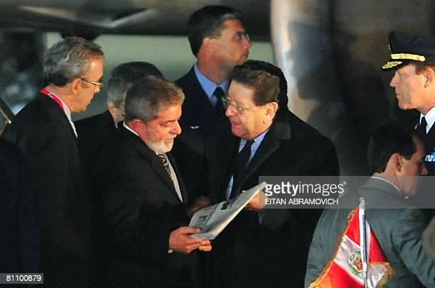 Brazilian President Luiz Inacio Lula Da Silva listens to Peruvian Minister of Labor Mario Pasco upon his arrival in Lima to take part in the V Latin...