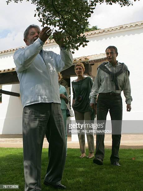 Brazilian President Luiz Inacio Lula da Silva looks at a fruit tree by Spanish Prime Minister Jose luis Rodriguez Zapatero and his wife Sonsoles...