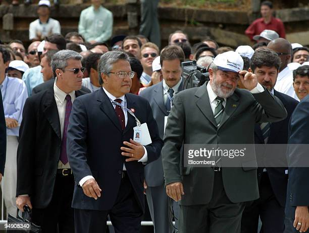 Brazilian President Luiz Inacio Lula da Silva right dons an Emraer cap as he is escorted by Embraer CEO Mauricio Botelho second from right at the...