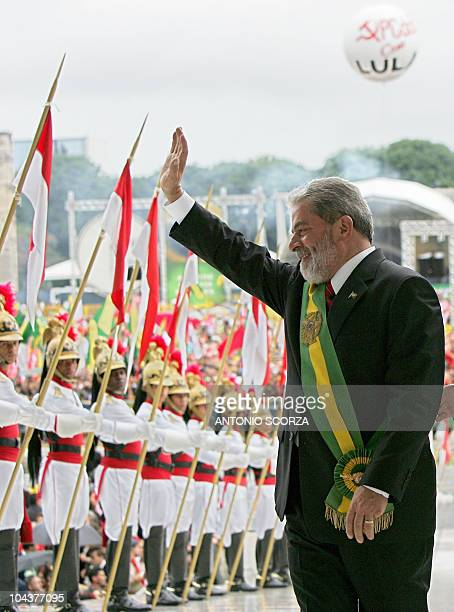 Brazilian President Luiz Inacio Lula da Silva waves to the public before climbing up the Planalto Palace's ramp to be sworn for a second four year...