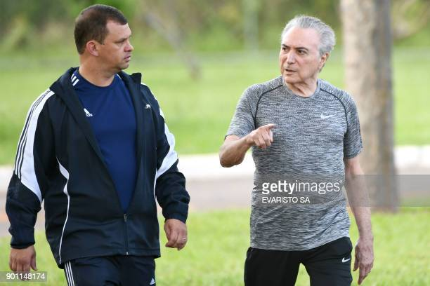 Brazilian President Michel Temer accompanied by his bodyguards takes a morning walk in the gardens of the Juburu residential palace in Brasilia on...