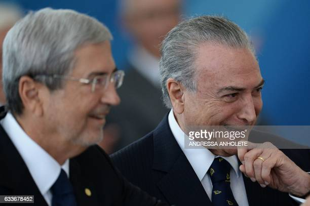 Brazilian President Michel Temer and Minister of Government Secretariat Antonio Imbassahy smile during the inauguration ceremony of the ministers of...
