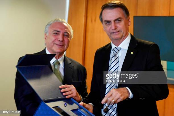 Brazilian President Michel Temer hands Brazilian presidentelect Jair Bolsonaro the keys of the transitional goverment's building during a meeting in...