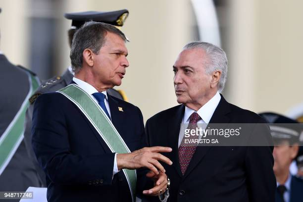 Brazilian President Michel Temer listens to acting Defence Minister Joaquim Silva e Luna during a parade on the Brazilian Army commemorative day at...