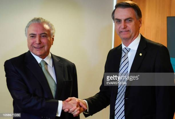 Brazilian President Michel Temer shakes hands with Brazilian presidentelect Jair Bolsonaro during a meeting in Brasilia on November 7 2018