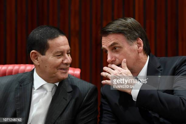 Brazilian Presidentelect Jair Bolsonaro and his VicePresidentelect Hamilton Mourao talk during a ceremony in which they received diploma that certify...