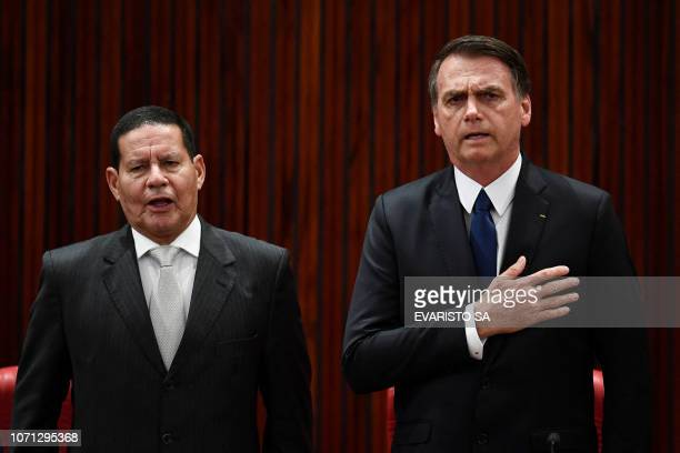 TOPSHOT Brazilian Presidentelect Jair Bolsonaro and his VicePresidentelect Hamilton Mourao listen to the national anthem during a ceremony in which...
