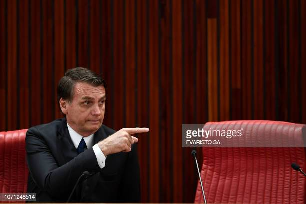 Brazilian Presidentelect Jair Bolsonaro delivers gestures during a ceremony in which he received a diploma that certifies he can take office as...
