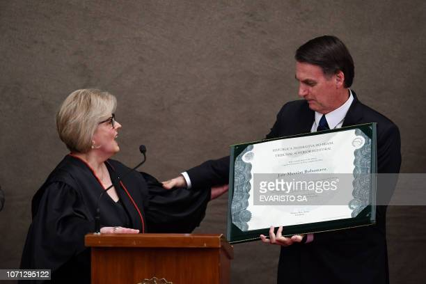 Brazilian Presidentelect Jair Bolsonaro displays a diploma that certifies he can take office as president next to Electoral Supreme Court president...