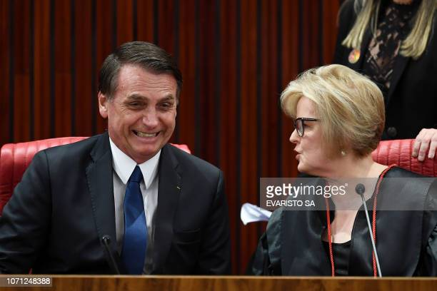 Brazilian Presidentelect Jair Bolsonaro speaks with Electoral Supreme Court president Justice Rosa Weber during a ceremony in which he received a...