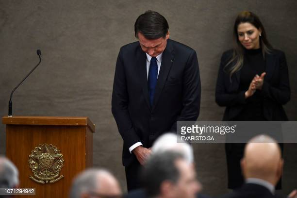 Brazilian Presidentelect Jair Bolsonaro takes a bow during a ceremony in which he received a diploma that certifies he can take office as president...
