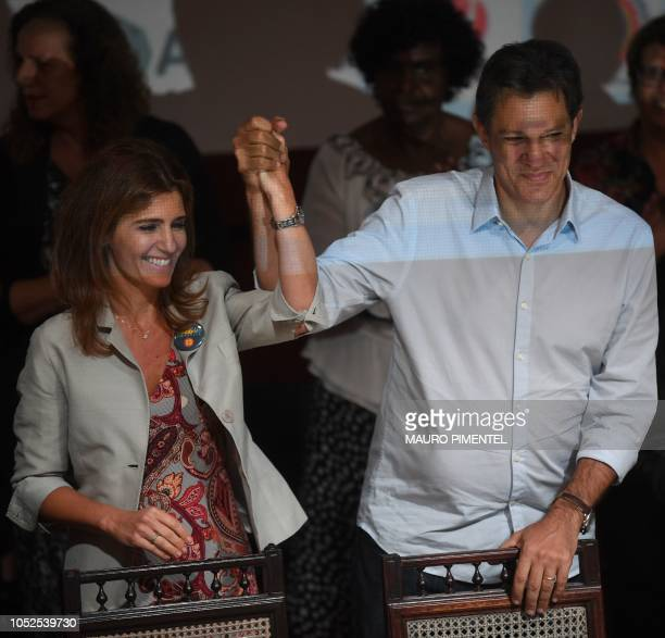 Brazilian presidential candidate for the Workers Party Fernando Haddad raises his his wife Ana Estela Haddad's hand during a visit to the Engineering...