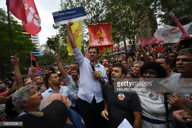 Brazilian presidential candidate for the Workers Party Fernando Haddad holds up a sign reading 'Marielle Franco Street' referring to the Brazilian...