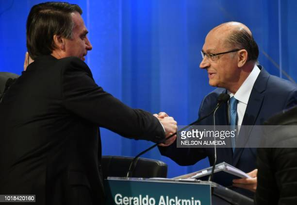 Brazilian presidential candidates Jair Bolsonaro and Geraldo Alckmin greet each other during the second presidential debate ahead of the October 7...
