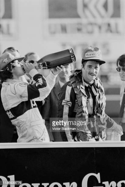 Brazilian racing driver and businessman Nelson Piquet winner of the European Grand Prix drinking from a bottle of Champagne next to British racing...